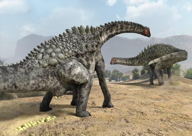 Самка жинозавра откладывает яйца